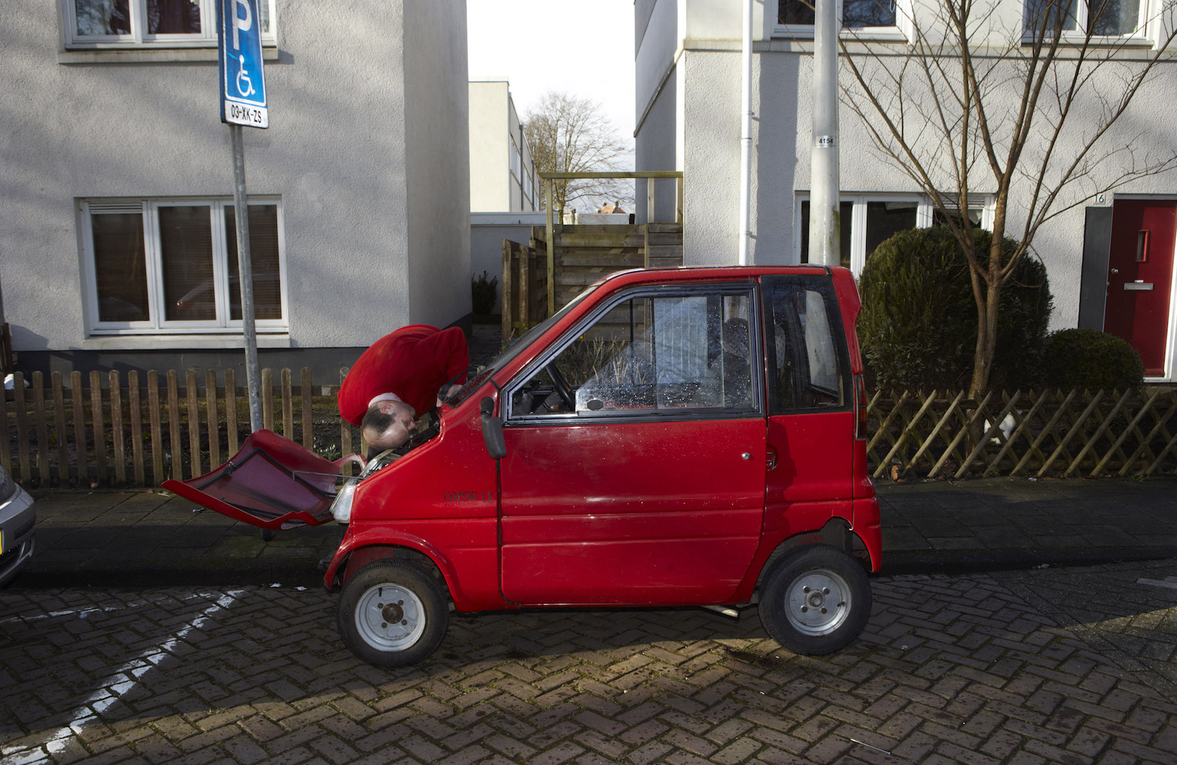 Nederland, 02-03-2015 Betondorp is een van de weinige wijken in Amsterdam waar de gentrificatie nog niet heeft toegeslagen. Een serie van een uniek stukje hoofddstad met een roemruchte geschiedenis. Hier kijkt een reperateur van Douwe Egberts naar de motor van de Canta van een vriendin: 'Lijkt eigenlijk precies op die van de motor van een koffiemachine.'